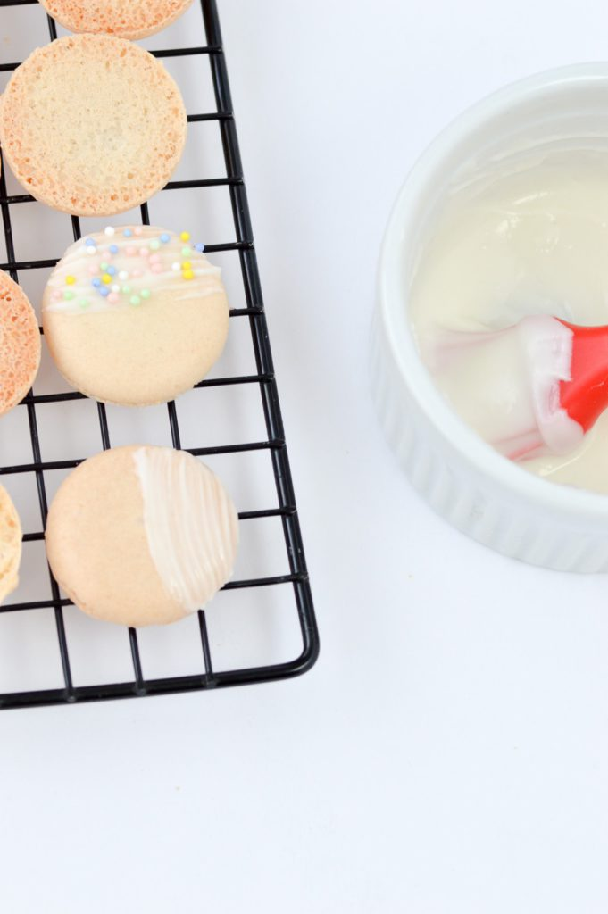 macarons painted with white chocolate and sprinkles