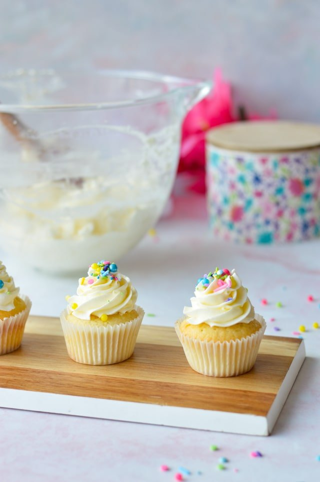 frosted cupcakes on a wood slab with a bowl of frosting in the background