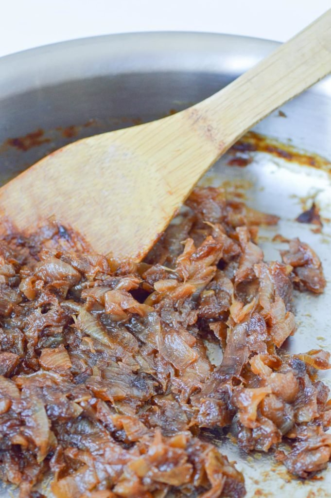Caramelized Onions in pan with wooden spoon