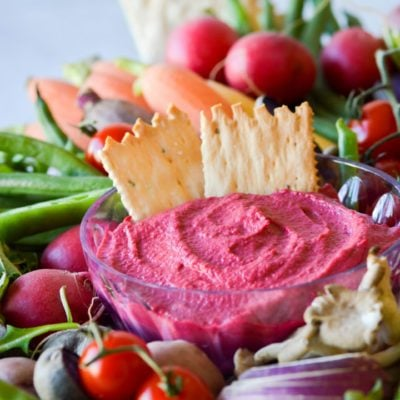 Roasted garlic beet dip with vegetables and crackers