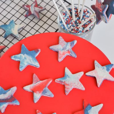 red white blue marble cookies on red cake stand and cooling tracy