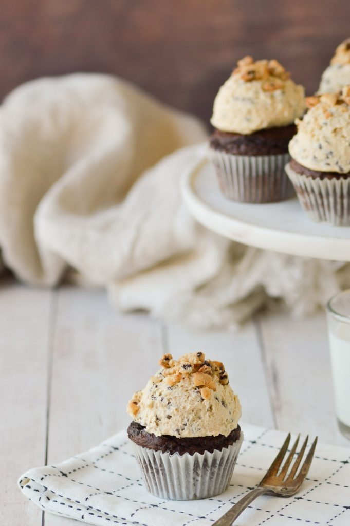 cookie dough on cupcake with cake stand and cupcakes in background