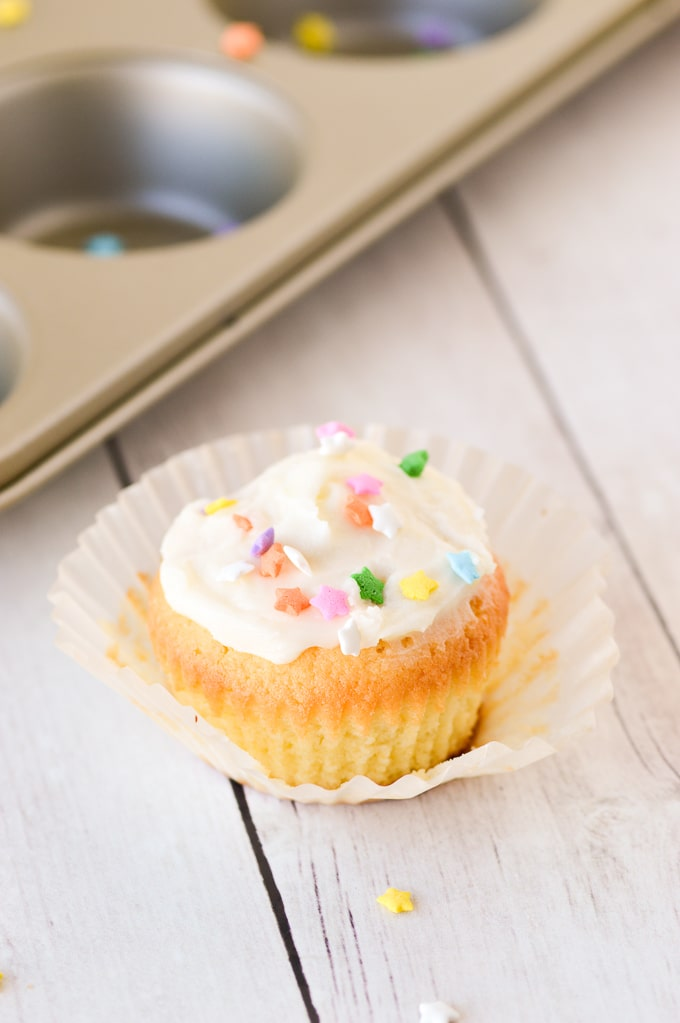 yellow cupcake in wrapper with frosting and sprinkles