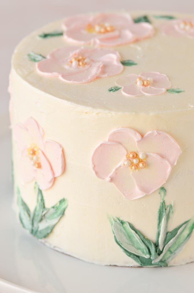 pink flowers painted in buttercream on cake side view