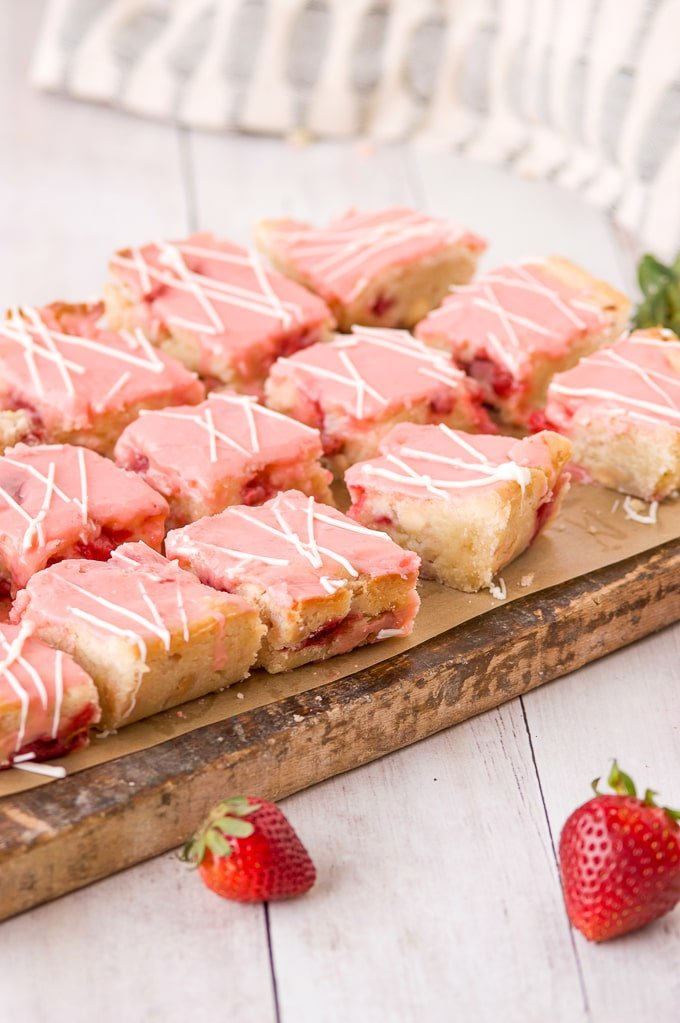 strawberry lemon blondies cut on wood cutting board