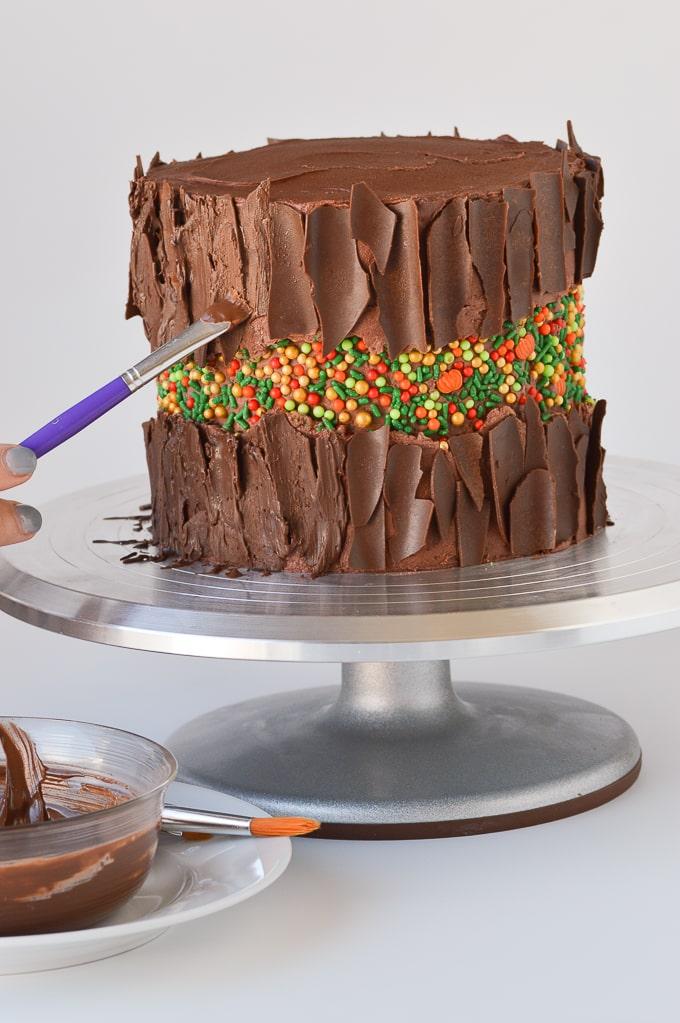 painting chocolate onto a cake to look like bark