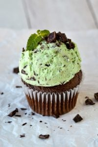 mint frosting on chocolate cupcake topped with chopped chocolate and mint