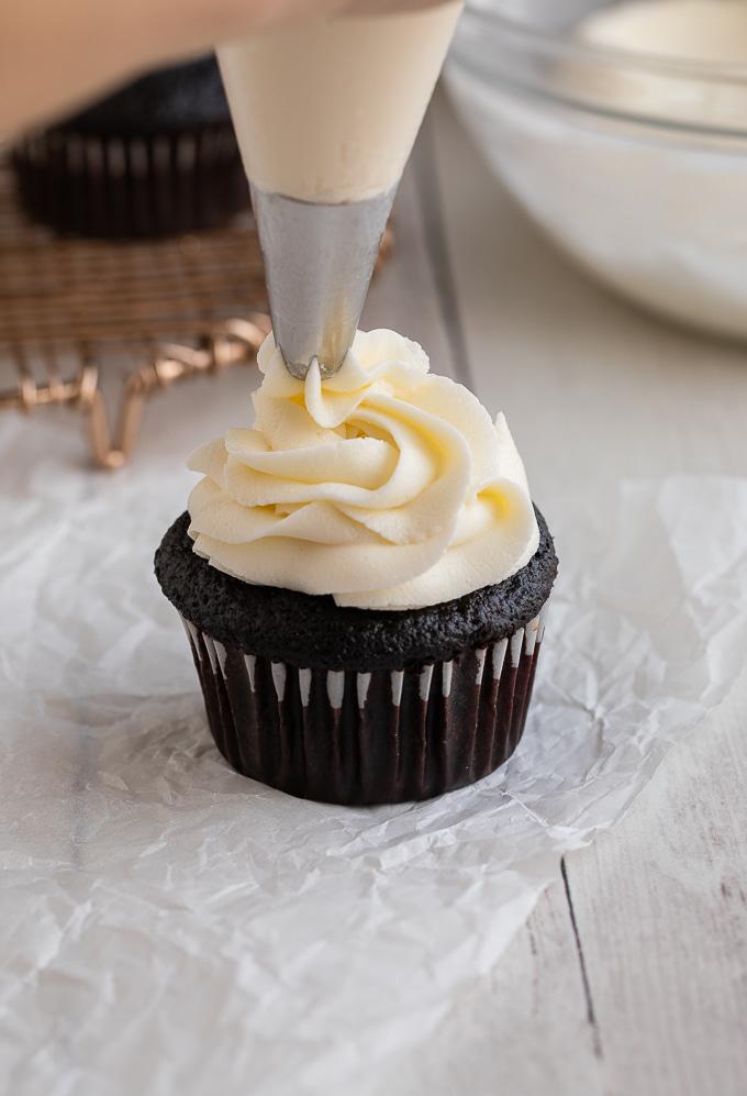 piping vanilla buttercream on chocolate cupcake