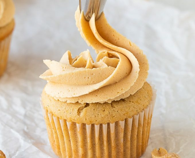 close up of piping peanut butter frosting on cupcake