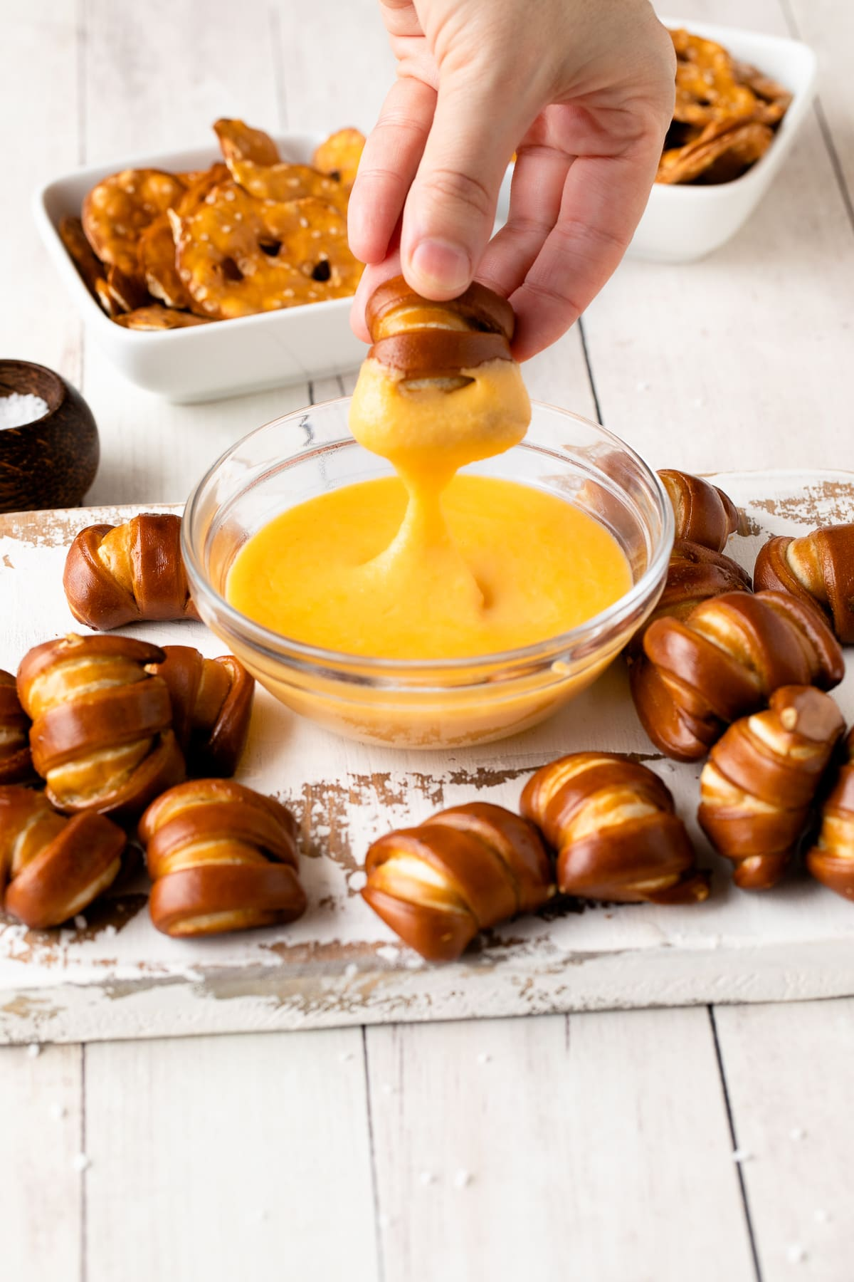cheese sauce in bowl with soft pretzel nugget being dipped in