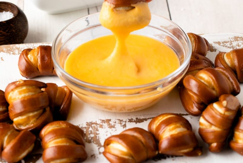 pretzel cheese dip with pretzel being dipped in sauce