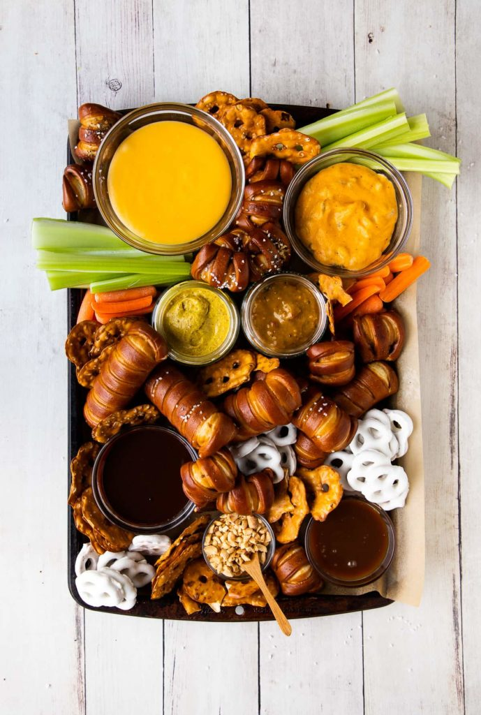 pretzel board with cheese dip, mustard, and chocolate sauce