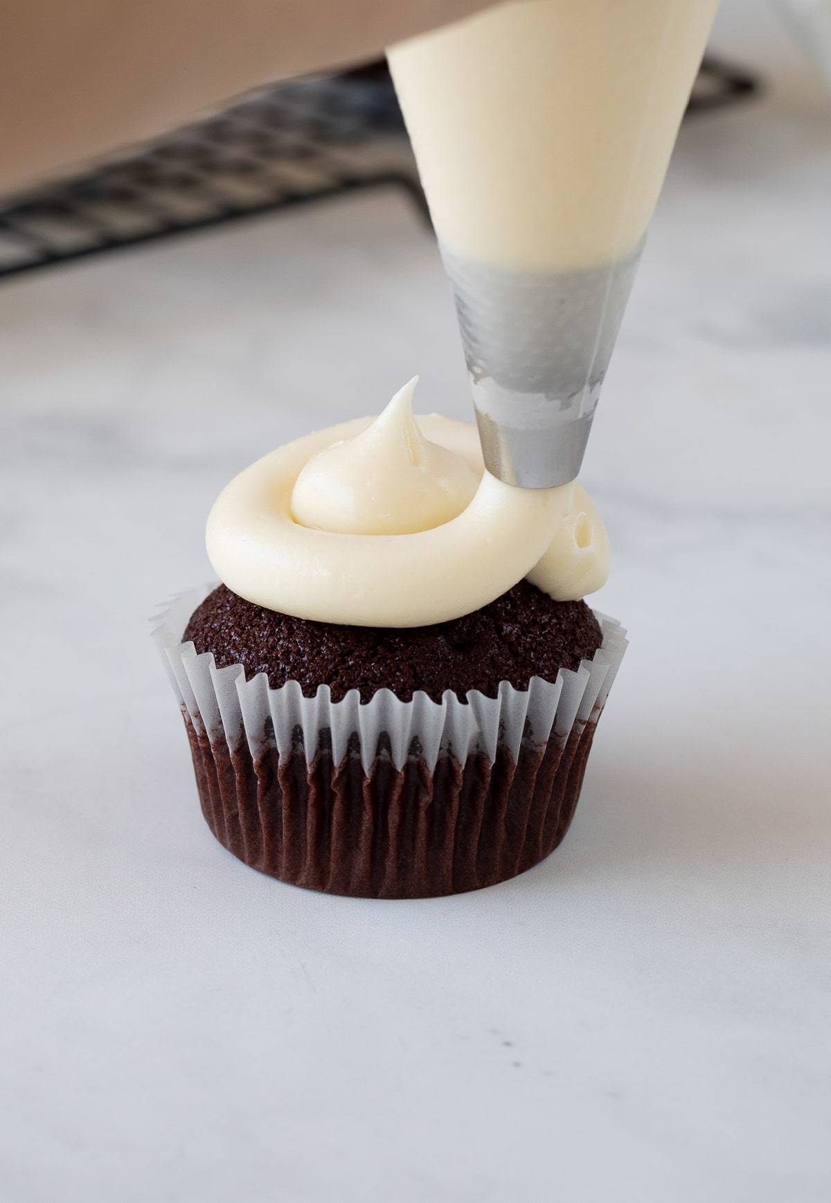 Cream Cheese Frosting being piped on cupcake